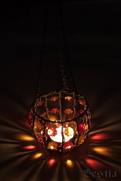Подвесной подсвечник на цепях в темноте с заженной свечой